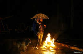 People gather around a bonfire during a blackout after an earthquake hit Chile's central zone, in Santiago, Aug. 23, 2014.