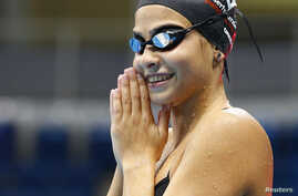 FILE - Syrian refugee team swimmer Yusra Mardini, 18, from Syria practices at the Olympic swimming venue at Olympic Park in Rio de Janeiro, Brazil, Jan. 8, 2016.