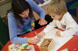 A teacher works with a student at the British School of Chicago, where lessons are individualized based upon how the student learns.