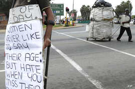FILE - A manl left, begs, as a another collects recyclable materials, at a street intersection in Johannesburg, South Africa, March 16, 2016.