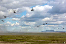 Photo provided by Russian Defense Ministry Press Service on Sept. 11, 2018 shows Russian military helicopters flying in the Chita region, Eastern Siberia, during the Vostok 2018 exercises in Russia.