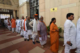 FILE - Members of Parliament stand in queue to cast their votes at Parliament House in New Delhi, India, July 17, 2017. Women reportedly hold only 12 percent of seats in both the lower and upper houses of parliament in the world's largest democracy.