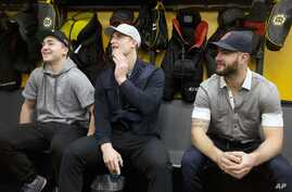 FILE - Boston Bruins players, from left, Frank Vatrano, Noel Acciari and Tyler Randell sit in the locker room during an end ofd season media availability at TD Garden in Boston.