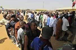 People wait in line at a registration center in Abuja, 15 Jan 2011.