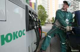 FILE - A worker fills up a car at Yukos gas station in Moscow.