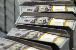 FILE - In this Sept. 24, 2013, file photo, freshly-cut stacks of $100 bills make their way down the line at the Bureau of Engraving and Printing Western Currency Facility in Fort Worth, Texas.