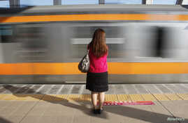 FILE - A woman waits to board a 'women only' passenger train during morning rush hours in Tokyo.