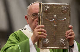 Pope Francis hoists the Gospel book as he celebrates a mass in St. Peter's Basilica at the Vatican, Oct. 5, 2014, to open the extraordinary Synod on the family.