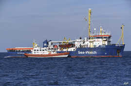 A coast guard boat approaches the German humanitarian group's rescue boat Sea Watch 3, to deliver food and blankets for the cold, off the coast of Syracuse, Italy, Jan. 27, 2019.