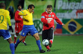 Chechnya leader Ramzan Kadyrov (r) fights for the ball with Brazil's 2002 World Cup-winning side player Dunga (c) during an exhibition match between Brazil's 2002 World Cup-winning side and 'team Kadyrov' in Grozny on March 8, 2011