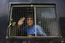 An unidentified Indian man accused on a 2002 riot case waves to supporters as he arrives at Ahmadabad's court, India, Thursday, June 2, 2016.
