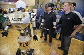 "FILE - Students control a ""Robocop"" during a demonstration at Florida International University, Feb. 12, 2014, in Miami."