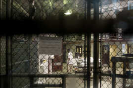 FILE - A prisoner walks through a communal pod inside an area of the Guantanamo Bay detention center known as Camp 6, at Guantanamo Bay Naval Base, Cuba, June 7, 2014.