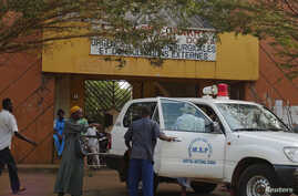 People walk in front of the entrance of Donka Hospital, where victims of the ebola disease are being treated, in Conakry March 28, 2014.