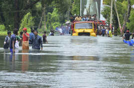 A truck carries people past a flooded road in Thrissur, in the southern Indian state of Kerala, Aug. 18, 2018. Rescuers used helicopters and boats Friday to evacuate thousands of people stranded on their rooftops following unprecedented flooding in t...
