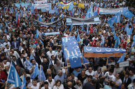 FILE - Uighurs living in Turkey and their supporters, some carrying coffins representing Uighurs who died in China's far-western Xinjiang region, chant slogans as they stage a protest in Istanbul against what they call China's oppression of Muslim Ui
