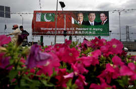 A Pakistani motorcyclist rides past a billboard showing pictures of Chinese President Xi Jinping, center, with Pakistan's President Mamnoon Hussain, left, and Prime Minister Nawaz Sharif welcoming Xi to Islamabad, Pakistan, April 19, 2015.