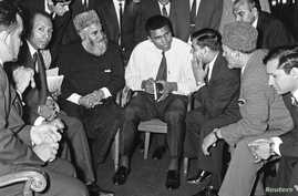 "FILE - Muhammad Ali speaks to Muslims holding a book called ""Towards Understanding Islam"" written by Sayyid Abul Ala Maududi in London, Britain, May 1966. Ali died late Friday in Phoenix, Arizona, June 3, 2016."