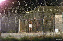 FILE - Marines at Camp X-Ray at the Naval Base at Guantanamo Bay, Cuba escort a newly arriving detainee into a processing tent after being showered.