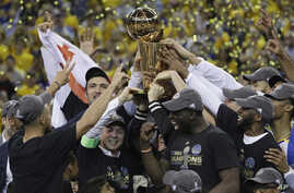 Golden State Warriors players, coaches and owners hold up the Larry O'Brien NBA Championship Trophy after Game 5 of basketball's NBA Finals between the Warriors and the Cleveland Cavaliers in Oakland, Calif., June 12, 2017.