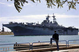 An Egyptian watches US amphibious assault ships USS Kearsarge as it sails at the Suez canal in Ismailia , Mar 2 2011