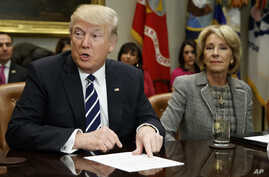 President Donald Trump accompanied by Education Secretary Betsy DeVos, speaks during a meeting with parents and teachers, Tuesday, Feb. 14, 2017, in the Roosevelt Room of the White House in Washington.