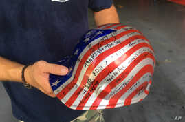Jon Hile, of Louisville, Ky., holds a hardhat, Aug. 19, 2016, with signatures of friends he met during his time volunteering at ground zero in Manhattan after the attacks of Sept. 11, 2001.