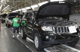 A Chrysler auto assembly worker walks along the final production line of the 2011 all-new Jeep Grand Cherokee at the Jefferson North Assembly Plant in Detroit, Michigan May 21, 2010. Chrysler Group LLC said on Friday it would hire almost 1,100 new wo