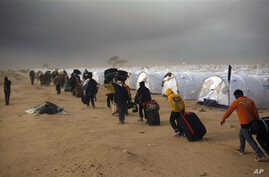 Men, who used to work in Libya and fled the unrest in the country, carry their belongings as they arrive during a sand storm in a refugee camp at the Tunisia-Libyan border, in Ras Ajdir, Tunisia, March 15, 2011