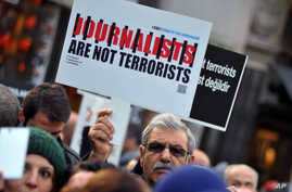 FILE - Turkish journalists are seen gathered to protest the jailing of opposition Cumhuriyet newspaper's editor-in-chief Can Dundar and Ankara representative Erdem Gul, in Istanbul, Dec. 26, 2015.