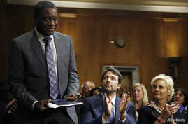 Actor, writer and director Ben Affleck, center, and Cindy McCain, right, applaud Denis Mukwege, left, Medical Director of the Panzi Hospital in the Congo, at the Senate Foreign Relations Committee, Capitol Hill, Washington, Feb. 26, 2014.