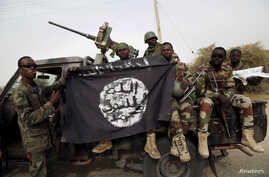 FILE PHOTO - Nigerian soldiers hold up a Boko Haram flag that they had seized in the recently retaken town of Damasak, Nigeria.