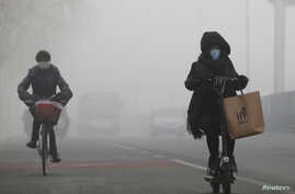 People ride amid the smog in Beijing, China, Feb.  14, 2017.