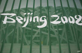 "FILE -  A protective fence shows a Beijing 2008 logo outside the National Stadium, known as the ""Birds Nest,"" in Beijing, China, Aug. 7, 2008. The IOC says 31 athletes in six sports have tested positive in a re-testing of their doping samples from th"