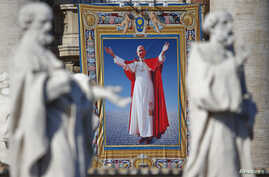 The tapestry with the image of Pope Paul VI is unveiled as Pope Francis celebrates the mass for his beatification in St. Peter's square at the Vatican, Oct. 19, 2014.