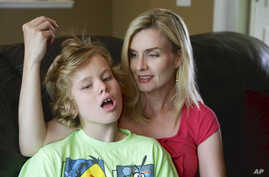 Colleen Jankovich looks over her 11-year-old autistic son, Matthew, who is non-verbal and requires 24/7 care, in Omaha, Nebraska, May 23, 2014.