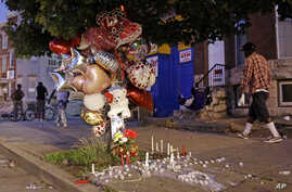 FILE - Balloons and candles mark a spot where a man was shot earlier in the week in Baltimore, July 30, 2015.