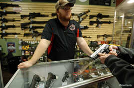 FILE - A gun store employee speaks to a customer about the purchase of a 9mm handgun in Bridgeton, Missouri, Nov. 13, 2014.