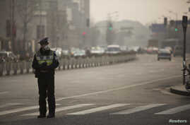 FILE - A policeman wearing a face mask stands on a road during a hazy day in Shanghai.