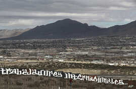 """Sunland Park, New Mexico, is seen over the U.S. border fence as a protester finishes painting the Spanish slogan """"Neither delinquents nor illegals, we are international workers"""" on the Anapra, Mexico, side of the fence, Feb. 26, 2017."""