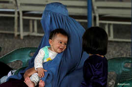 An Afghan refugee woman waits with her children to be repatriated to Afghanistan, at the United Nations High Commissioner for Refugees  office on the outskirts of Peshawar, Pakistan April 3, 2017.