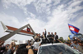 President of the Cambodia National Rescue Party (CNRP) Sam Rainsy (C) speaks to supporters over a loudspeaker, after arriving at Phnom Penh International Airport in Phnom Penh July 19, 2014.