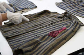 A conservator at the U.S. Holocaust Memorial Museum's conservation and research center points out a hidden pocket on a piece of clothing worn by a prisoner at a Nazi concentration camp.
