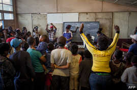 Voters reacts as an electoral officer holds up a ballot during ballot counting for the second round of Madagascar's presidential election at a polling station in Antananarivo, Dec. 19, 2018.