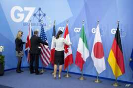 Workers adjust the flags of a Group of Seven meeting in Brussels, Belgium, June 5, 2014. G-7 foreign ministers are meeting Monday and Tuesday in Tuscany, Italy.