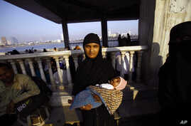 FILE - A Muslim woman holds her child and stands at the Haji Ali Dargah in Mumbai, India.