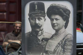 Tourists looking at exhibits in Sarajevo museum, including portraits of Archduke Franz Ferdinand and Sofia von Hochenberg, in Sarejevo, Saturday, June 28, 2014