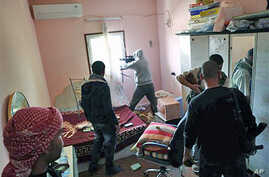 Libyan rebel fighters are seen in the room of a house while a comrade fires from a window at pro-Gadhafi troops in the besieged city of Misrata, the main rebel holdout in Gadhafi's territory, April 22, 2011