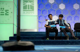 Jairam Hathwar, 13, of Painted Post, N.Y., left, and Nihar Janga, 11, of Austin, Texas, right, pat each other on the back as they hear that they will likely be announced co-champions after a drawn-out battle that did indeed end in them being named co