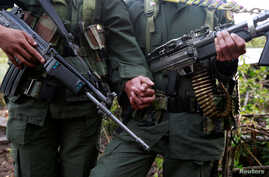 A couple from the 51st Front of the Revolutionary Armed Forces of Colombia (FARC) pose for the camera at a camp in Cordillera Oriental, Colombia, Aug. 16, 2016.